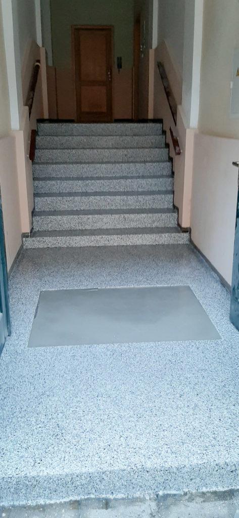 Kamenný koberec na schodech bytového domu.
